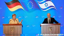 German Chancellor Angela Merkel, and Israeli Prime Minister Naftali Benett, give a joint press conference following a cabinet meeting at the King David hotel in Jerusalem, on October 10, 2021. - Germany's outgoing Chancellor Angela Merkel said Israel's security will be a top priority for every German government during a farewell tour in the Jewish state today, as she prepares to end a 16-year term in office. (Photo by Menahem KAHANA / AFP)