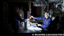 People shop in a grocery store under a portable electric light during a power cut near Bhamdoun, Lebanon, October 9, 2021. REUTERS/Mohamed Azakir
