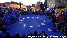 Participants hold a large EU flag as they take part in a pro-EU demonstration following a ruling of the Constitutional Court against the primacy of EU law in Poland, in Warsaw on October 10, 2021. - Tens of thousands of Poles rallied on October 10 in defence of their country's EU membership, after Poland's top court last week issued a landmark ruling against the primacy of EU law. The pro-EU demonstrations were called by former EU chief Donald Tusk, now leader of the country's main opposition grouping, Civic Platform, who has warned of the prospect of a Polexit. (Photo by Wojtek Radwanski / AFP) (Photo by WOJTEK RADWANSKI/AFP via Getty Images)