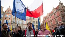 People hold up an EU flag and a Polish flag tied together as they take part in a pro-EU demonstration following a ruling of Poland's Constitutional Court against the primacy of EU law, at the Dlugi Targ Square in Gdansk, northern Poland, on October 10, 2021. - Tens of thousands of Poles rallied on October 10 in defence of their country's EU membership, after Poland's top court last week issued a landmark ruling against the primacy of EU law. The pro-EU demonstrations were called by former EU chief Donald Tusk, now leader of the country's main opposition grouping, Civic Platform, who has warned of the prospect of a Polexit. (Photo by MATEUSZ SLODKOWSKI / AFP) (Photo by MATEUSZ SLODKOWSKI/AFP via Getty Images)