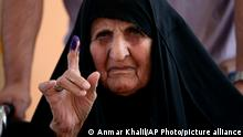 An Iraqi woman shows her ink-stained finger after casting her vote during parliamentary elections, inside a polling station in Najaf, Iraq, Sunday, Oct. 10, 2021. Iraq closed its airspace and land border crossings on Sunday as voters headed to the polls to elect a parliament that many hope will deliver much needed reforms after decades of conflict and mismanagement. (AP Photo/Anmar Khalil)