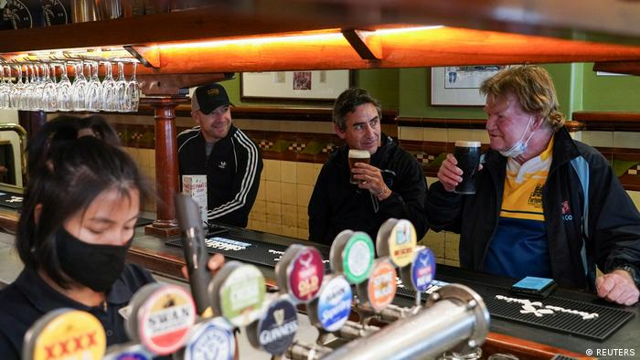 Customers Brian O'Mara, Darrell Forman and Doug Thomas drink beers together at the Fortune of War pub, on the first morning of pubs and many other businesses re-opening to vaccinated people in Sydney