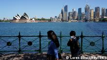 06.10.2021 FILE PHOTO: People in protective face masks walk along the harbour waterfront across from the Sydney Opera House during a lockdown to curb the spread of coronavirus disease (COVID-19) outbreak in Sydney, Australia, October 6, 2021. REUTERS/Loren Elliott/File Photo