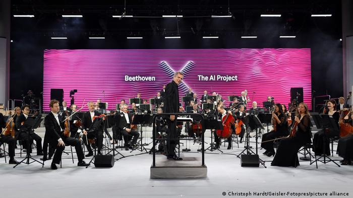 Orquestra e regente com letreiro Beethoven X - The AI Project ao fundo