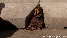 A girl sits between concrete barriers in Kabul, Afghanistan October 7, 2021. REUTERS/Jorge Silva TPX IMAGES OF THE DAY