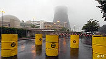 Yellow nuclear waste drums in front of power plant