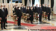 Members of Tunisia's new government stand during their swearing-in ceremony, in Tunis, Tunisia October 11, 2021. Tunisian Presidency/Handout via REUTERS ATTENTION EDITORS - THIS IMAGE WAS PROVIDED BY A THIRD PARTY NO RESALES. NO ARCHIVES.