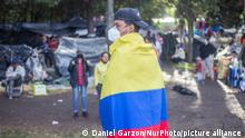 An immigrant with a flag in the colors of the flag of his country, Venezuela while waiting for buses to take him to the border city, Cúcuta, Colombia, on July 2, 2020, in the coming days. They lived for about a month and 6 days in a makeshift camp with 450 Venezuelans from the pandemic. (Photo by Daniel Garzon Herazo/NurPhoto)