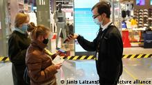 (211011) -- RIGA, Oct. 11, 2021 (Xinhua) -- People have their COVID-19 vaccination certificates checked before entering a shopping mall in Riga, Latvia, Oct. 11, 2021. The Latvian government declared new emergency rules to stem the country's rapidly rising COVID-19 incidence. The government also decided to declare a state of emergency, which came into effect on Monday, and will remain in force until Jan. 11. (Photo by Janis Laizans/Xinhua)