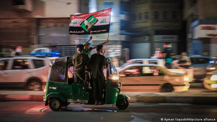 Supporters waving banner on rickshaw in traffic