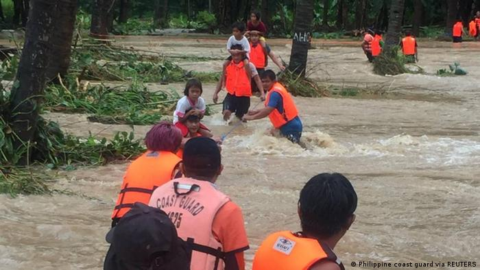 People cross floodwaters caused by tropical cyclone Kompasu during an evacuation