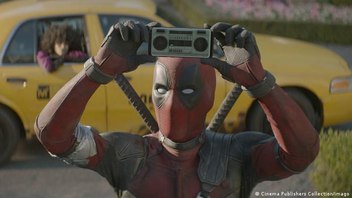 Сцена из фильма Дэдпул: актер Райан Рейнольдс держит над головой мини радиоприемник.