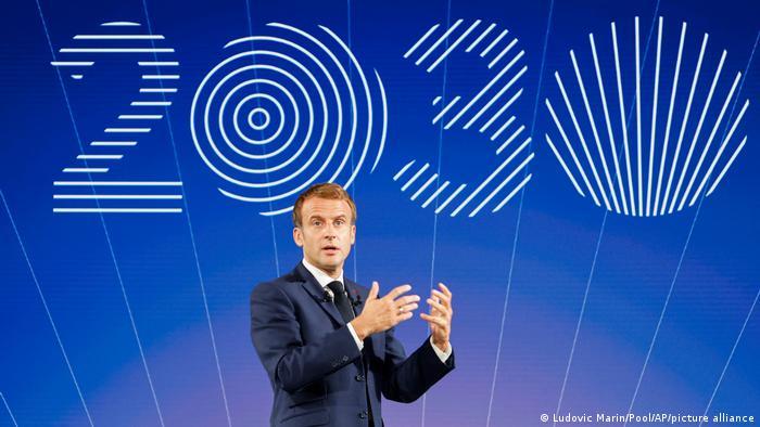 Emmanuel Macron speaking in front of 2030 sign