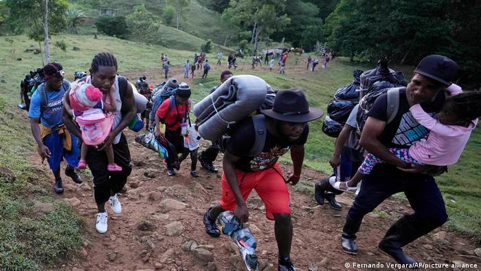 Menschen tragen Gepäck und Kinder auf dem Arm über eine unwegsames Gelände den Berg hoch.