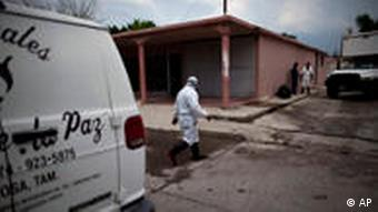 A worker in a protective suit walks to a funeral home where the bodies of 72 people killed by the Zetas drug gang are held inside a refrigerated truck