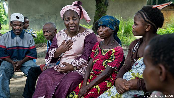 Julienne Lusenge sits surrounded by survivors of conflict violence