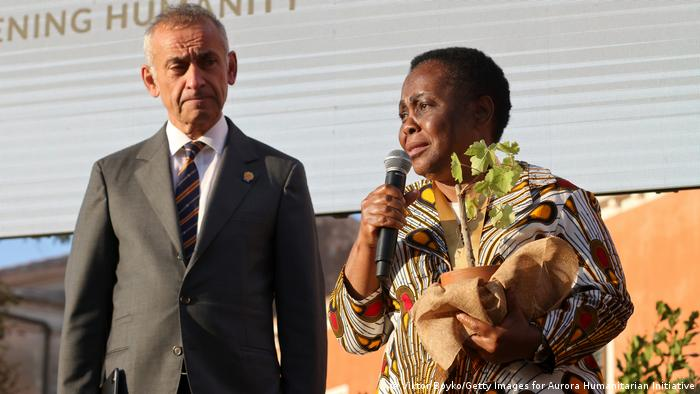 Julienne Lusenge delivers her acceptance award holding a plant with Lord Ara Darzi looking on