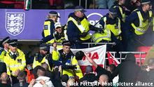 Hungary fans clash with police officers in the stands during the World Cup group I Qualifying soccer match between England and Hungary at Wembley Stadium, London, Tuesday, Oct. 12, 2021. Hungary supporters have clashed with police during the start of a World Cup qualifier against England at Wembley Stadium. Disorder by Hungary fans — including racism — during the home match against England in Budapest last month led to Hungary having to play Saturday's game against Albania in an empty stadium. (Nick Potts/PA via AP)