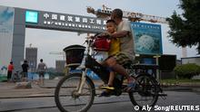 People ride a bicycle past the construction site of Guangzhou Evergrande Soccer Stadium, a new stadium for Guangzhou FC developed by China Evergrande Group, in Guangzhou, Guangdong province, China September 26, 2021. REUTERS/Aly Song