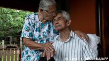 Clementina Espinoza (L), 92, kisses her husband Agustin Espinoza, 100, pose in Nicoya, Costa Rica, on August 27, 2021. - The couple lives in one of the five Blue Zones of the world, where longevity is a characteristic in a higher than usual number of people. (Photo by Ezequiel BECERRA / AFP)