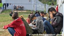 Mehrere Migranten sitzen auf einer Wiese vor Containern in der Zentralen Erstaufnahmeeinrichtung für Asylbewerber (ZABH) des Landes Brandenburg. Im Zuge der deutlich gestiegenen Registrierung von Migranten in Brandenburg informierte sich der Innenminister des Landes Brandenburg, Stübgen (CDU), vor Ort über die aktuelle Situation.