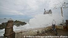 A cyclist is splashed by a crashing wave prior the landfall of tropical storm Pamela, on the boardwalk in Mazatlan, Mexico, Tuesday, Oct. 12, 2021. Hurricane Pamela weakened to a tropical storm Tuesday afternoon as it meandered off Mexico's Pacific coast. Forecasters said it was expected to regain strength overnight and be a hurricane when making landfall somewhere near the port of Mazatlan Wednesday. (AP Photo/Roberto Echeagaray)
