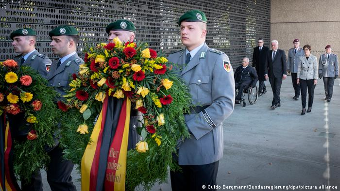 Soldiers carry a wreath honoring fallen comrades as President Steinmeier and other politicians follow