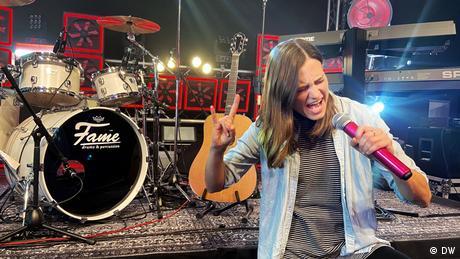 Rachel Stewart von Meet the Germans steht vor einem Schlagzeug und singt in ein Mikrofon und macht dazu den Metaler-Gruß.