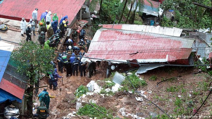 Rescuers search for victims in a house buried by a landslide
