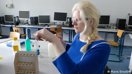 Die sehbehinderte Schülerin Alexandra Dunayeva hält ein Reagenzglas mit einer Zange