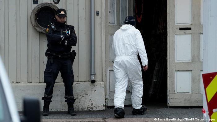 A police forensic passes a Norwegian policeman standing guards outside during investigations