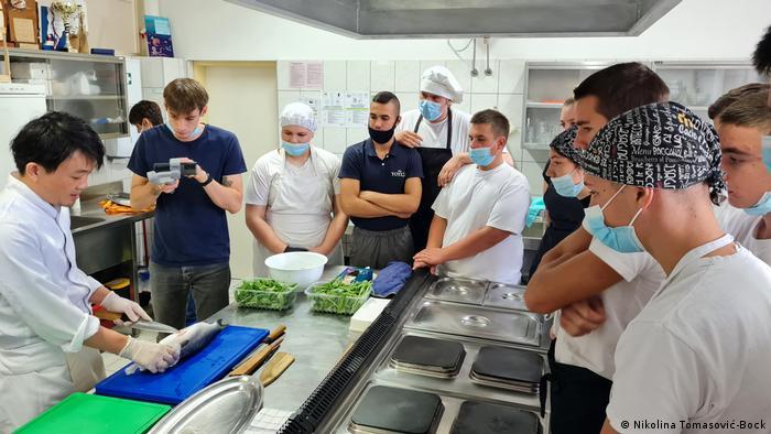 Chef Ippei Uemura pokazuje učenicima filetiranje ribe