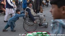 A boy pushes a man in a wheelchair trough a market in Kabul, Afghanistan, Tuesday, Oct. 12, 2021. (AP Photo/Ahmad Halabisaz)