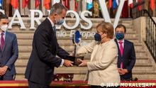 Germany's Chancellor Angela Merkel (R) receives the Carlos V European Award from Spain's King Felipe VI during a ceremony at the Royal Monastery of Yuste, in Cuacos de Yuste, on October 14, 2021. - The Carlos V award is given to leaders who have stood out for their commitment to the process of the European union or their contribution to the exaltation of the cultural, scientific and historical values of Europe. (Photo by Jero MORALES / POOL / AFP)