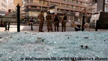 14.10.2021, Beirut, Libanon, Glass from broken windows litters a street as Lebanese army soldiers stand guard after deadly clashes erupted along a former 1975-90 civil war front-line between Muslim Shiite and Christian areas, in Ain el-Remaneh neighborhood, Beirut, Lebanon, Thursday, Oct. 14, 2021. Lebanese officials say at least six people were killed and dozens were wounded in armed clashes that erupted in Beirut during protests organized by the militant Hezbollah group and its allies against the lead investigator into last year's massive blast at the city's port. (AP Photo/Bilal Hussein)