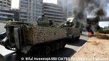 14.10.2021, Beirut, Libanon, Lebanese army soldiers stand guard on their armored vehicle as supporters of the Shiite Hezbollah and Amal groups burn garbage containers to block a road during a protest in Beirut, Lebanon, Thursday, Oct. 14, 2021. Armed clashes broke out in Beirut Thursday during a protest against the lead judge investigating last year's massive blast in the city's port, as tensions over the domestic probe boiled over. (AP Photo/Bilal Hussein)