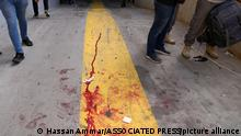 14.10.2021, Beirut, Libanon, Supporters of a Shiite group allied with Hezbollah stand next to blood from an injured comrade during armed clashes that erupted during a protest in the southern Beirut suburb of Dahiyeh, Lebanon, Thursday, Oct. 14, 2021. It was not immediately clear what triggered the gunfire, but tensions were high along a former civil war front-line between Muslim Shiite and Christian areas. (AP Photo/Hassan Ammar)
