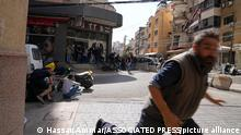 14.10.2021, Beirut, Libanon, A man runs to take cover as supporters of a Shiite group allied with Hezbollah fire weapons during armed clashes that erupted during a protest in the southern Beirut suburb of Dahiyeh, Lebanon, Thursday, Oct. 14, 2021. It was not immediately clear what triggered the gunfire, but tensions were high along a former civil war front-line between Muslim Shiite and Christian areas. (AP Photo/Hassan Ammar)