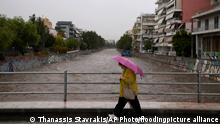 14.10.2021 A woman with an umbrella walks over a gushing river during a storm in southern Athens, Thursday, Oct. 14, 2021. Severe storms swept across Greece Thursday, flooding hundreds of homes in Athens and prompting evacuations on the island of Evia that was ravaged by summer wildfires. (AP Photo/Thanassis Stavrakis)