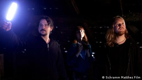 A still from the film Endlich Tacheles shows three people in the dark, looking slightly up, one holding a bright light