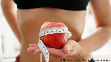 A woman holding an apple surrounded by measuring tape