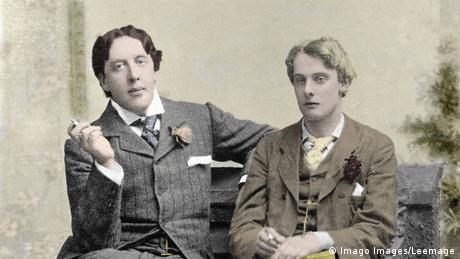 Oscar Wilde (à esquerda) sentado em um banco com o lorde Alfred Douglas (à direita). Ambos estão fumando cigarro.