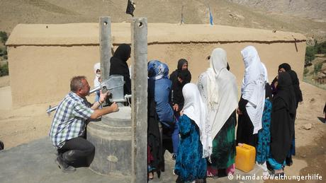 Stefan Recker kneels while speaking to a group of women and girls in Afghanistan