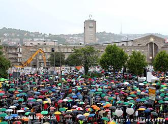 Protesters with umbrellas in front of the station