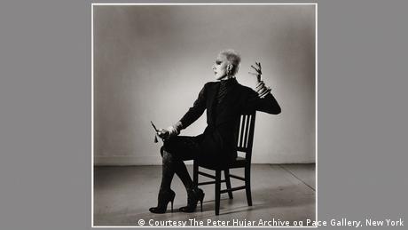 Ein Foto zeigt eine Person auf einem Stuhl sitzend in einer exaltierten Pose.