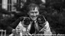 """Conservative MP David Amess with his pugs, Lily and Boat at the Westminster Dog of the Year competition at Victoria Tower Gardens in London on Oct. 10, 2013. British police say a man has been arrested after a reported stabbing in eastern England. News outlets say the victim is Conservative lawmaker David Amess. The Essex Police force said officers were called to reports of a stabbing in Leigh-on-Sea just after noon Friday. It said """"a man was arrested shortly after"""