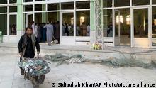 People view the damage inside of a mosque following a suicide bombers attack in the city of Kandahar, southwest Afghanistan, Friday, Oct. 15, 2021. Suicide bombers attacked a Shiite mosque in southern Afghanistan that was packed with worshippers attending Friday prayers, killing several people and wounding others, according to a hospital official and a witness. (AP Photo/Sidiqullah Khan)