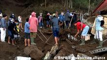 (211016) -- BALI, Oct. 16, 2021 (Xinhua) -- Photo provided by Indonesia's National Disaster Management Agency (BNPB) shows people evacuating victims after a 4.8-magnitude quake and landslide hit Bali, in Indonesia, Oct. 16, 2021. Three people were killed and seven others suffered broken bones with another one still buried under rubbles of a building after a 4.8-magnitude quake damaged houses in Indonesia's resort island of Bali early Saturday. (BNPB/Handout via Xinhua)