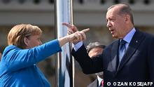 Turkish President Recep Tayyip Erdogan (R) and German Chancellor Angela Merkel (L) gesture as they pose in Istanbul on October 16, 2021. (Photo by Ozan KOSE / AFP)