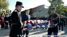 French President Emmanuel Macron, center, layis a wreath near the Pont de de Bezons (Bezons bridge) Saturday, Oct. 16, 2021 in Colombes near Paris. Emmanuel Macron becomes the first French president to commemorate the brutal repression of an Oct 17, 1961 demonstration during which at least 120 Algerians were killed during a protest to support Algerian independence. The bridge was borrowed 60 years ago by Algerian demonstrators who arrived from the neighboring slum de Nanterre at the call of the Algerian independence supporters based in France. (AP Photo/Rafael Yaghobzadeh, Pool)